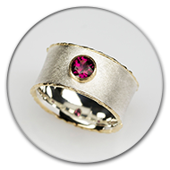 Ring from 925 silver with charred sides made from 18k gold, rhodolith set in 18k gold