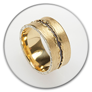 Ring from 18k gold and charred 925 silver with intermittend brilliants set along the sides